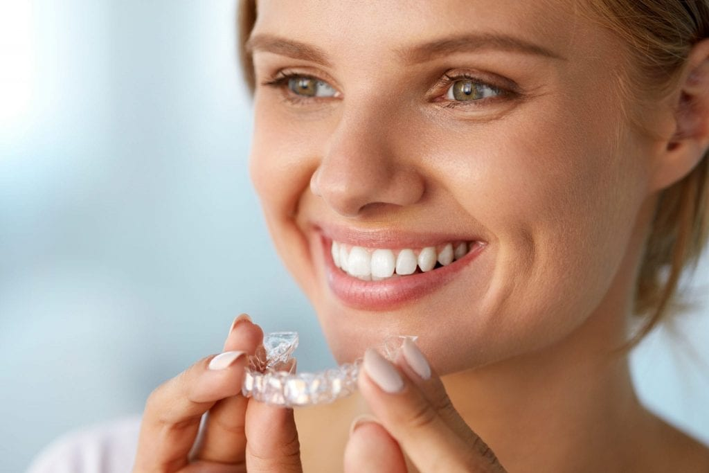 dental checkup. Invisalign Dentist. Smiling Woman With White Teeth Holding Teeth Whitening Tray. High Resolution Image. r ben alexander dds mckinney tx